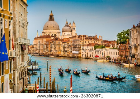 Beautiful view of Gondolas on famous Canal Grande with Basilica di Santa Maria della Salute in golden evening light at sunset in Venice, Italy - stock photo