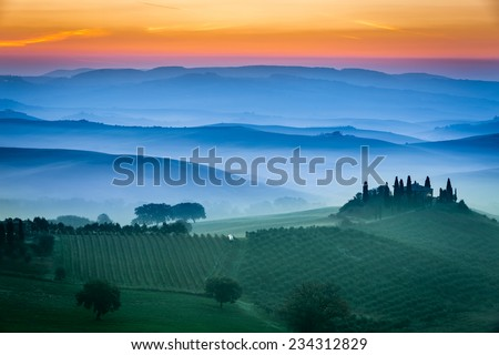 Beautiful view of green fields and meadows at sunset in Tuscany - stock photo