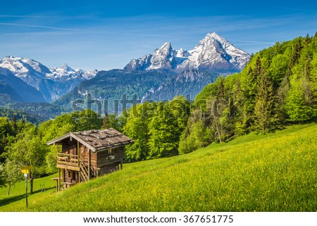 Beautiful view of idyllic mountain scenery in the Alps with fresh green mountain pastures with flowers and old traditional mountain lodge in springtime - stock photo