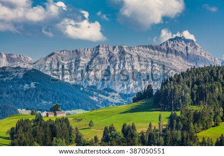 Beautiful view of idyllic mountain scenery in the Alps with green meadows and famous Saentis summit in the background on a sunny day with blue sky and clouds in summer, Appenzellerland, Switzerland - stock photo