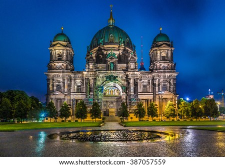 Beautiful view of illuminated facade of historic Berlin Cathedral at Lustgarten park with famous TV tower in the background in twilight during blue hour at dusk, Berlin Mitte district, Germany - stock photo