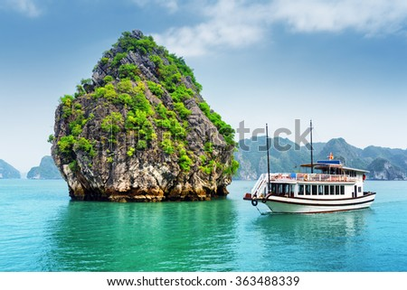 Beautiful view of karst isle and tourist boat in the Ha Long Bay (Descending Dragon Bay) at the Gulf of Tonkin of the South China Sea, Vietnam. The Halong Bay is a popular tourist destination of Asia - stock photo