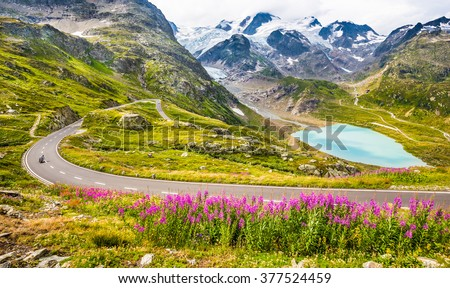 Beautiful view of motorcyclist driving on winding mountain pass road in the Alps through gorgeous scenery with mountain tops, ice glaciers, lakes and green pastures with blooming flowers in summer - stock photo