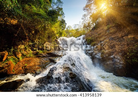 Beautiful view of natural waterfall with crystal clear water among green woods in summer. The sun is shining through foliage of trees. Amazing forest landscape in Vietnam. Blue sky in background. - stock photo