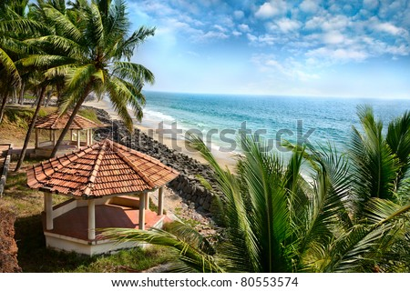 Beautiful view of ocean, beach, summer houses and palm trees in Varkala, Kerala, India - stock photo