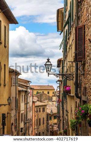 Beautiful view of old traditional houses and idyllic alleyway in the historic town of Volterra, province of Pisa, Tuscany, Italy - stock photo