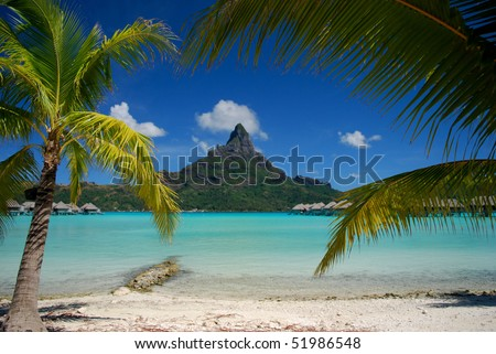 Beautiful view of Otemanu mountain view on Bora Bora framed by coconut palms - stock photo