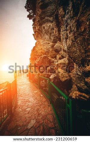 Beautiful view of path with handrails in high mountains at sunset  - stock photo