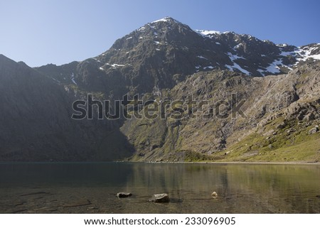 beautiful view of snowdon, north wales across a lake with clear blue skies - stock photo