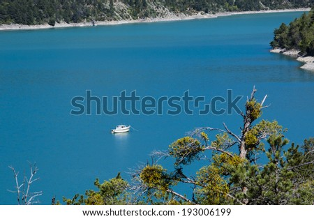 Beautiful view of St.Croix lake in Verdon with a white anchored boat. (Provence, France) - stock photo
