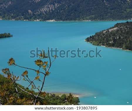 Beautiful view of St.Croix lake in Verdon with white sailing boats. (Provence, France) Selective focus on the tree twigs. - stock photo