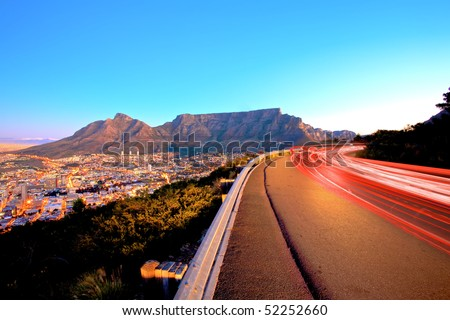 Beautiful view of Table Mountain in Cape Town from Signal Hill and some light streeks from cars. - stock photo