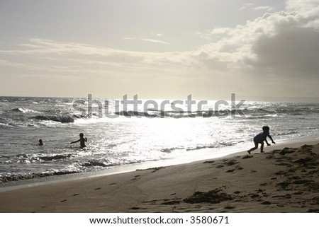 Beautiful view of the beach and ocean with children playing. - stock photo
