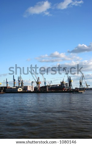 Beautiful view of the cranes and logistics at teh harbour of Hamburg with blue sky - stock photo