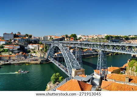 Beautiful view of the Dom Luis Bridge over the Douro River and the historic centre of Porto on the blue sky background in Portugal. Porto is one of the most popular tourist destinations in Europe. - stock photo