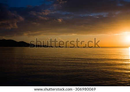 Beautiful view of the Golden sunset, sun, clouds, sea and the island. Spain, Mallorca