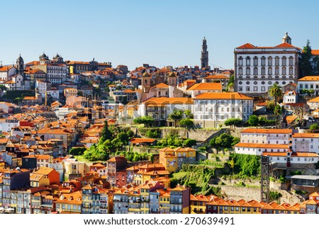 Beautiful view of the historic centre of Porto in Portugal. The bell tower of Torre dos Clerigos is visible on the blue sky background. Porto is one of the most popular tourist destinations in Europe. - stock photo