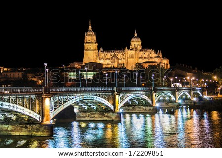 Beautiful view of the historic city of Salamanca with New Cathedral and Enrique Esteban bridge at night, Castilla y Leon region, Spain - stock photo