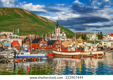 Beautiful view of the historic town of Husavik with traditional colorful houses and traditional fisherman boats lying in the harbor in golden evening light at sunset, northern coast of Iceland - stock photo