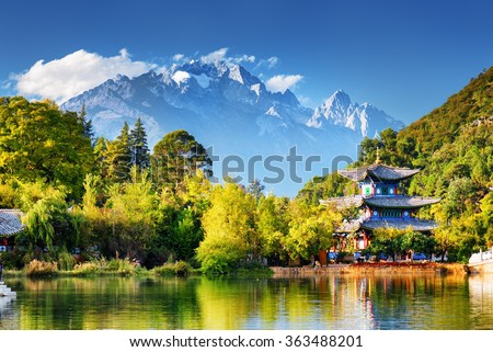 Beautiful view of the Jade Dragon Snow Mountain and the Moon Embracing Pavilion on the Black Dragon Pool in the Jade Spring Park, Lijiang, Yunnan province, China.