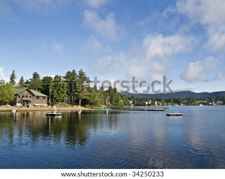 Beautiful view of the Mirror Lake, located in Lake Placid (Adirondack Mountains National Park - New York) with reflections of the clouds and the trees on the water. - stock photo