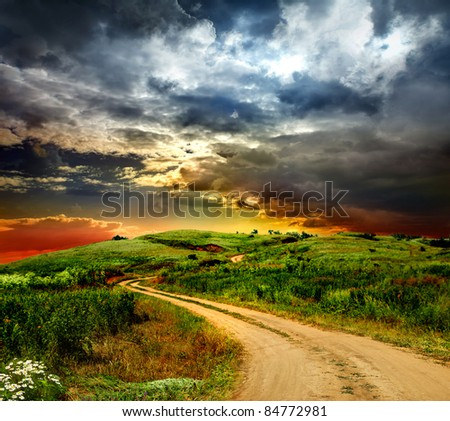 beautiful view of the sunset in a field on a rural road - stock photo