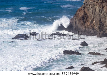 beautiful view of this section of beach in California with waves crashing into the rocks and mountain