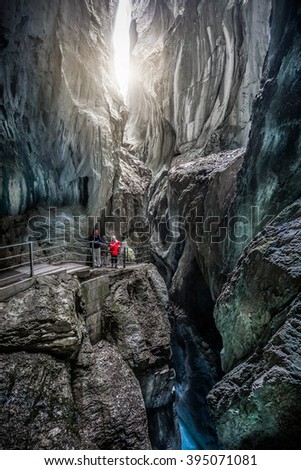 Beautiful view of tourists hiking on trail through famous mystical Rosenlaui glacier gorge (Rosenlaui Gletscherschlucht), a UNESCO World Heritage since 2001, in the Bernese Alps in summer, Switzerland - stock photo