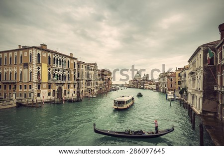 Beautiful view of traditional Gondola and boats on Canal Grande with Basilica di Santa Maria della Salute church in background at a cloudy day, Venice (Venezia), Italy, Europe, Vintage filtered style  - stock photo