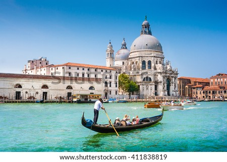 Beautiful view of traditional Gondola on Canal Grande near Piazza San Marco with historic Basilica di Santa Maria della Salute in the background on a sunny day with blue sky in summer, Venice, Italy - stock photo