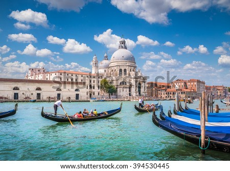 Beautiful view of traditional Gondolas on Canal Grande with historic Basilica di Santa Maria della Salute in the background on a sunny day with blue sky and clouds in Venice, Italy - stock photo