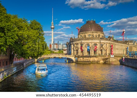 Beautiful view of UNESCO World Heritage Site Museumsinsel (Museum Island) with excursion boat on Spree river and famous TV tower in the background in beautiful evening light at sunset, Berlin, Germany - stock photo