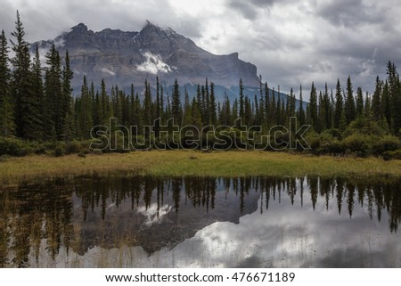 Beautiful view on a peaceful lake with a reflection, and rocky mountains in the background. Taken in Banff National Park, Alberta, Canada, during a cloudy day.