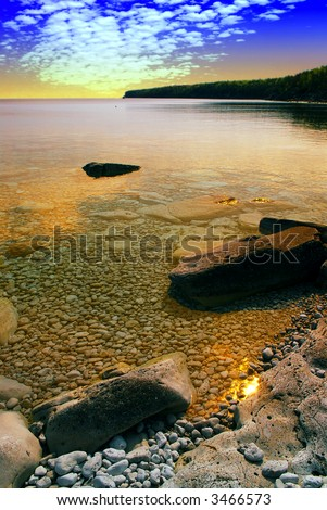 Beautiful view on a rocky shore with clear water and golden reflections at sunset. Georgian Bay, Canada. - stock photo