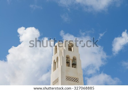 Beautiful view on belfry of the Cathedral Of Candlemas Of The Lord in a sky at summer sunny day.Cathedral is located in famous touristic center Fira town.Santorini (Thira) island.Cyclades.Greece. - stock photo