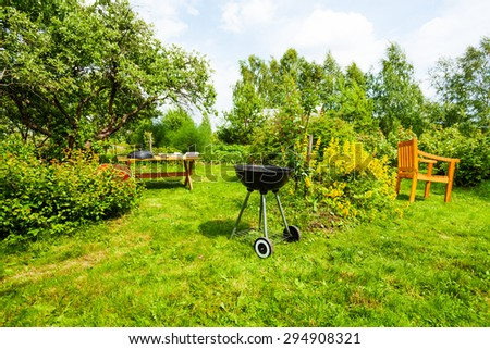 Beautiful view on garden with grill, table, chair - stock photo