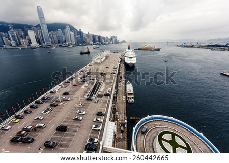 Beautiful view on Hong Kong harbour with cloudy sky and city buildings on background - stock photo