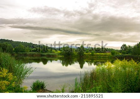 beautiful view on the lake with the green forest and white sky background. Backgrounds - stock photo