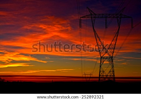 Beautiful view with one electricity tower on dramatic colorful sky at evening time, cloudy sky at orange sunset - stock photo