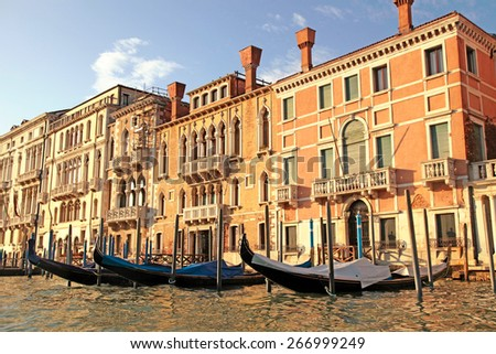 Beautiful view with typical venetian houses and gondola on the Grand Canal, Venice, Italy.  Gondola is one of the symbols of Venice and major mode of touristic transport in Venice.  - stock photo