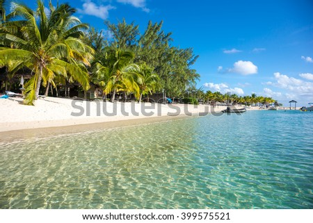 Beautiful views of the resort on the island of Mauritius. Transparent ocean, white sand, palm trees on a background of clouds - stock photo
