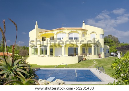 Beautiful villa with a healthy garden and a covered pool at Algarve, south of Portugal - stock photo