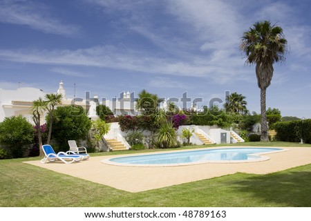 Beautiful villa with a healthy garden and a refresh water pool at Algarve, south of Portugal - stock photo
