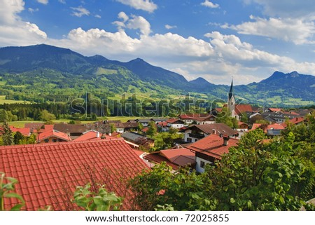 Beautiful village in the valley surrounded by Alp mountains. Summer day, blue sky with clouds. - stock photo