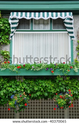 Beautiful vintage building window with flowers in the historic butchart gardens (over 100 years in bloom), vancouver island, british columbia, canada