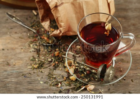 Beautiful vintage composition with herbal tea, on wooden table - stock photo
