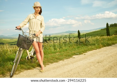 beautiful vintage girl sitting next to bike, summer time  - stock photo