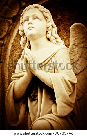 Beautiful vintage image of a praying angel in sepia shades - stock photo