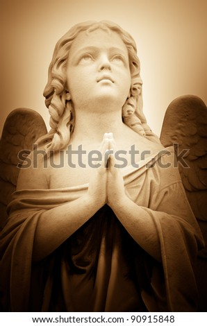 Beautiful vintage image of a praying angel in sepia shades with light illuminating his face - stock photo