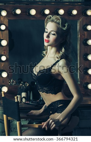 Beautiful vintage style pinup young woman in sexy lingerie. Glamour hairstyle. Sensual body posing. Retro underwear